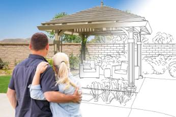 a couple looking at their pergola being built by Mackay Carports