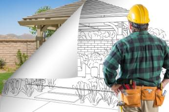 a Mackay Carports worker looking at the blueprint of the decking project of a house